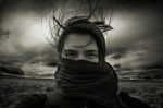 """[PHOTO: """"Jessie,"""" a CC-licensed image by LeTiger.] A young woman, nose and mouth covered with a scarf in foreground of flat, windswept landscape"""